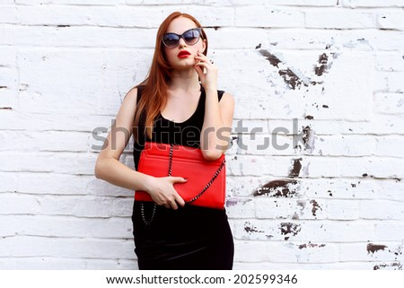 Portrait  gorgeous fashion woman in black dress with red clutch and fashionable sunglasses near white wall - stock photo