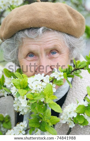 portrait granny smells  white flowers - stock photo