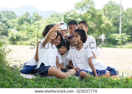 Portrait group  of childrens taking a selfie in the field under the tree - stock photo