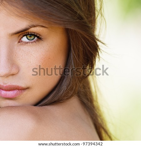 portrait half face of beautiful sexy girls with dark hair and bare shoulders seductively on green background - stock photo