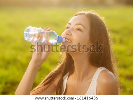 Portrait half face of young woman drink water bottle at summer green park - stock photo