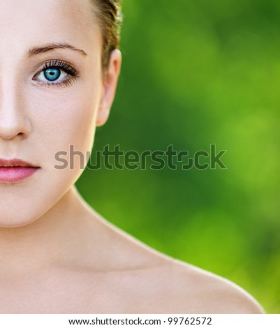 Portrait half of face beautiful sexy young woman with bare shoulders seductively at summer green park - stock photo
