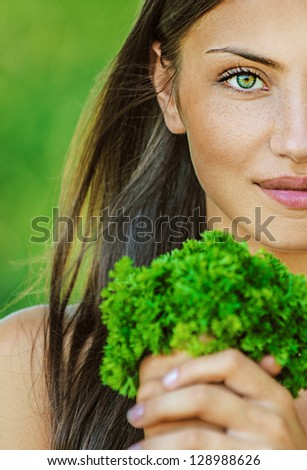 Portrait half of face young beautiful woman with bare shoulders holding bunch of parsley, on green background summer nature.