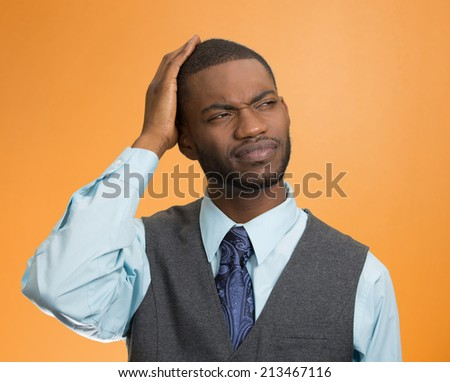 Portrait handsome company business man thinking, daydreaming trying hard to remember something looking up isolated orange background. Human emotions, facial expression, feeling reaction, body language - stock photo