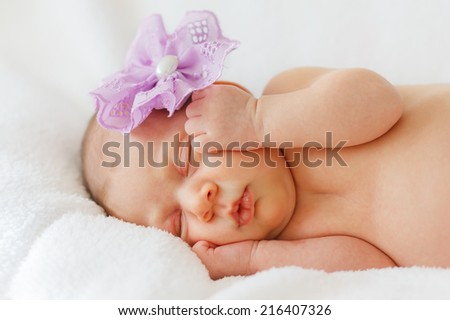 Portrait happy baby girl new born sleeping with purple flower. Selective focus