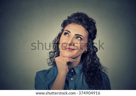 Portrait happy beautiful woman thinking looking up isolated on grey wall background with copy space. Human face expressions, emotions, feelings, body language, perception - stock photo