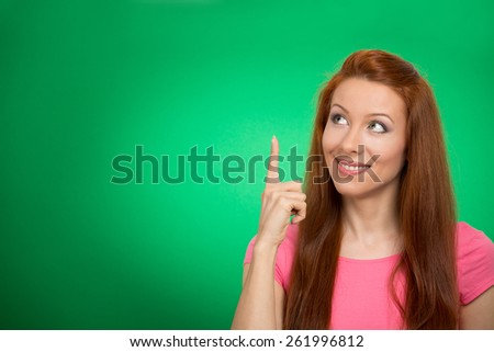 Portrait happy beautiful woman thinking looking up pointing with finger at blank copy space isolated green background. Positive human face expressions, emotions, feelings body language, perception - stock photo