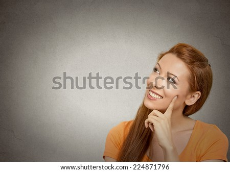 Portrait happy beautiful woman thinking looking up smiling isolated grey wall background with copy space. Human face expressions, emotions, feelings, body language, perception, imagination - stock photo