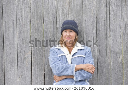 Portrait happy confident smiling attractive single mature woman outdoor, wearing warm bonnet and wool jacket, timber wall background, copy space. - stock photo