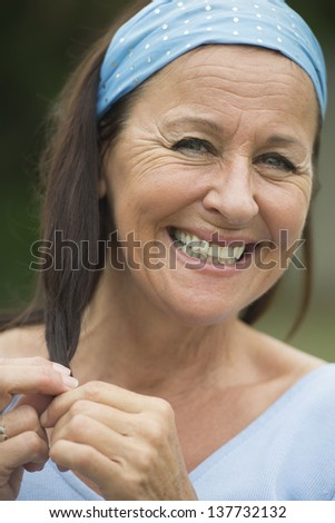 Portrait happy funny smiling attractive mature woman outdoor, joyful facial expression, enjoying retirement and leisure lifestyle, wearing blue shirt and headband, with blurred background. - stock photo