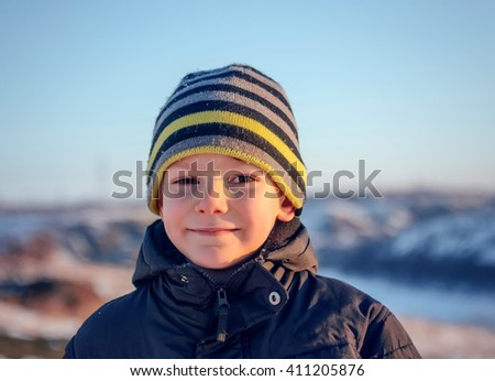 Portrait Happy little boy in winter clothing having fun in fresh white winter snow in evening light - stock photo