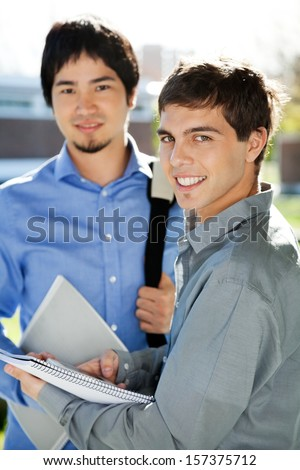 Portrait happy male students with books standing in university campus