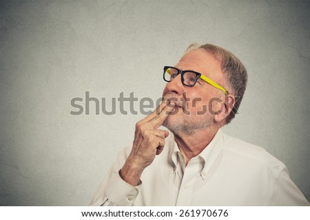 Portrait happy mature man in white shirt thinking looking up isolated grey wall background with copy space. Human face expressions, emotions, feelings, body language, perception - stock photo