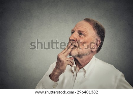 Portrait happy mature man thinking looking up isolated on gray wall background with copy space. Human emotions, feelings, body language, perception - stock photo