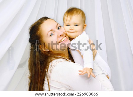 Portrait happy mother and baby together in bedroom