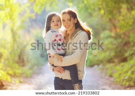 Portrait happy mother and child in autumn outdoors - stock photo