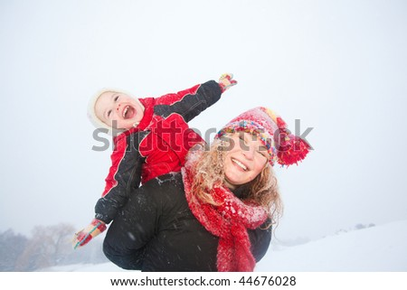 Portrait happy mother and child together in snow  laughing, smiling. - stock photo