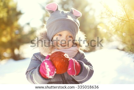 Portrait happy smiling child with red christmas ball in winter day - stock photo