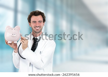 Portrait happy smiling doctor holding listening to piggy bank with stethoscope standing in hospital hallway on clinic office windows background  - stock photo