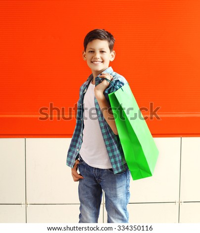 Portrait happy smiling little boy teenager with shopping bag in city over red background - stock photo