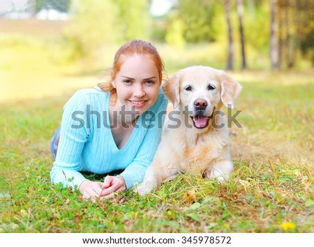 Portrait happy smiling owner woman and Golden Retriever dog lying on grass