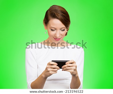 Portrait happy, smiling woman texting on her smart phone, isolated green background. Communication concept. Positive facial expressions, emotion, feelings, good news. Internet, game, phone addiction - stock photo