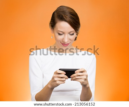 Portrait happy, smiling woman texting on her smart phone, isolated orange background. Communication concept. Positive facial expressions, emotion, feelings, good news. Internet, phone addiction - stock photo