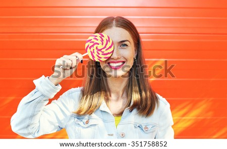 Portrait happy smiling woman with sweet caramel lollipop over colorful orange background - stock photo