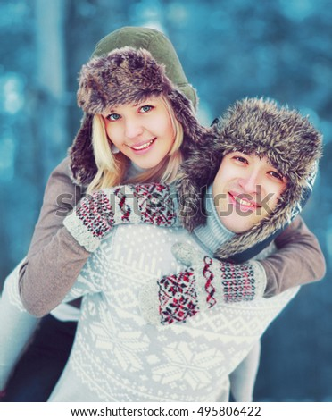 Portrait happy smiling young couple in winter day having fun, man giving piggyback ride to woman, life moment