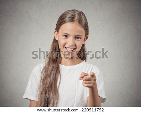 Portrait happy teenager girl pointing finger laughing smiling surprised by something isolated grey wall background. Positive human emotion facial expression feeling reaction body language - stock photo
