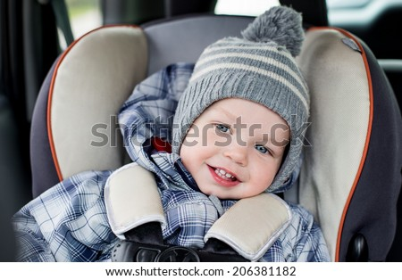 portrait happy toddler  boy sitting in the car seat  - stock photo