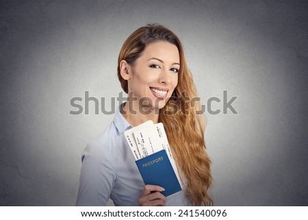 Portrait happy tourist young woman holding passport holiday flight ticket standing isolated on grey wall background. Positive human emotions face expression. Travel vacation getaway trip concept  - stock photo