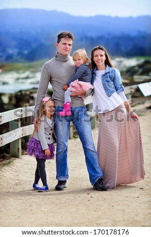 portrait happy young family of four in casual fashion wear scenic view background - stock photo