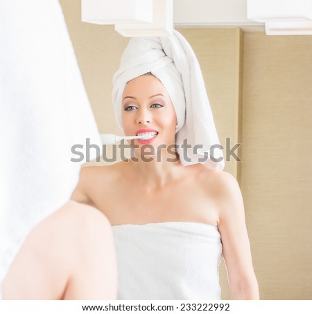 Portrait happy young woman brushing teeth looking in mirror. Personal oral hygiene dentistry concept. Positive face expression  - stock photo