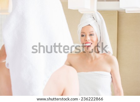 Portrait happy young woman brushing teeth looking in mirror. Personal oral hygiene, fresh breath, preventive dentistry concept. Positive face expression  - stock photo