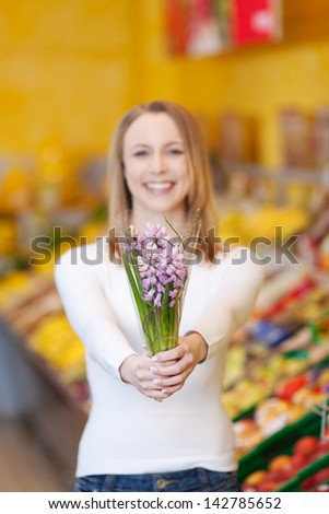 Portrait happy young woman holding flower bouquet in grocery store