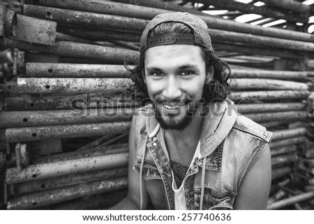 Portrait hipster fashion man dressed in�  jeans jacket sitting on the iron frame begraund smiling - stock photo