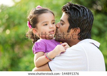 portrait if father kissing daughter in out door against nature background, Indian man kissing his daughter. - stock photo