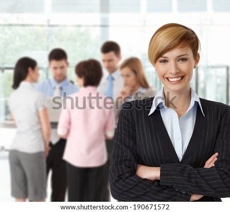 Portrait if happy businesswoman with colleagues working in background. - stock photo