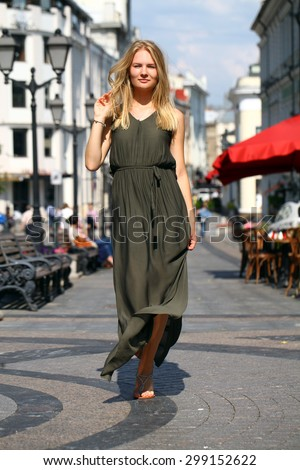 Portrait in full growth, attractive young blonde woman in long dress walking in summer street