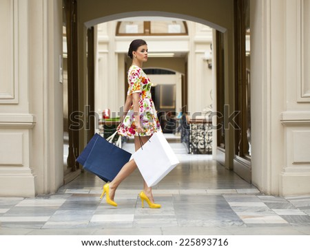 Portrait in full growth, Beautiful young woman in red flowers dress in the shop - stock photo