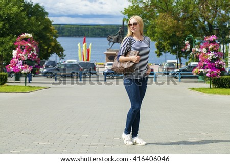 Portrait in full growth the young beautiful women in blue jeans and in striped vest on the background summer street - stock photo