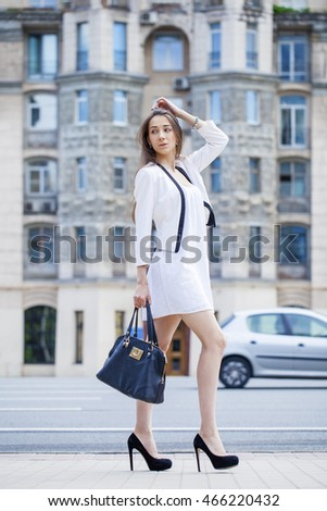 Portrait in full growth, young beautiful brunette woman in white dress on the street, summer outdoors