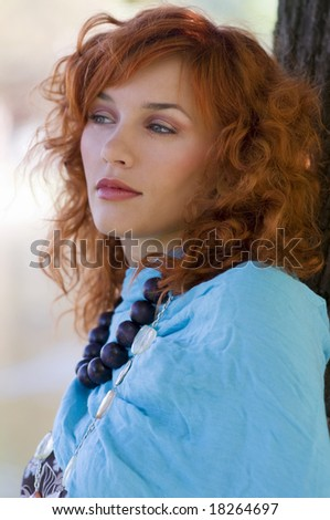 portrait in the park of a red haired girl with a blue scarf and necklace