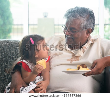 Portrait Indian family at home. Grandparent and grandchild eating cake. Asian people living lifestyle. Grandfather and granddaughter. - stock photo