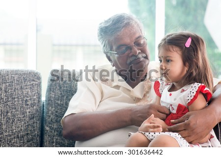 Portrait Indian family at home. Grandparent and grandchild playing together. Asian people living lifestyle. Grandfather and granddaughter. - stock photo
