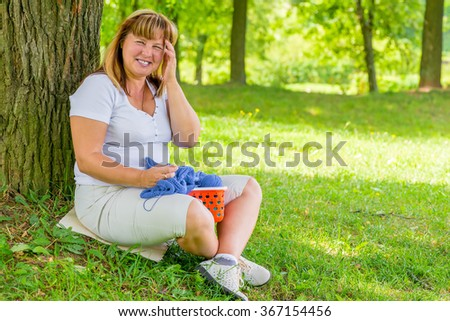 portrait laughing 50 year old woman in the park dedicated to knitting - stock photo