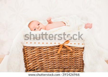 portrait little baby (child) lying in a wooden basket. newborn. son. boy. - stock photo