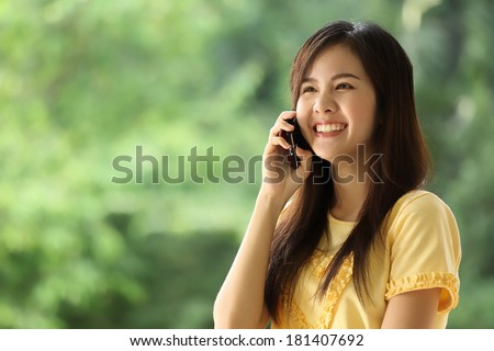 portrait lovely girl type information with her mobile phone in the nature garden s