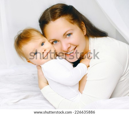 Portrait lovely smiling mother and baby in bed - stock photo